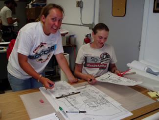 Two students smiling for a camera as they work on their project