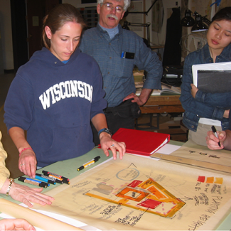 Students and teachers looking over a design plan