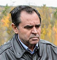 Photograph of Dr. Zydi Teqja outdoors in autumn in front of trees of yellow and orange