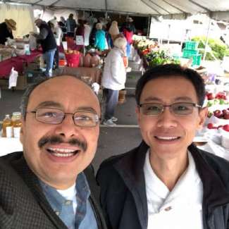 Alfonso takes a picture at farmer's market