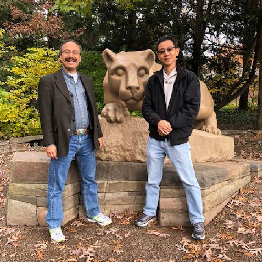 Professor Alfonso Morales stands in front of a statue at Penn State